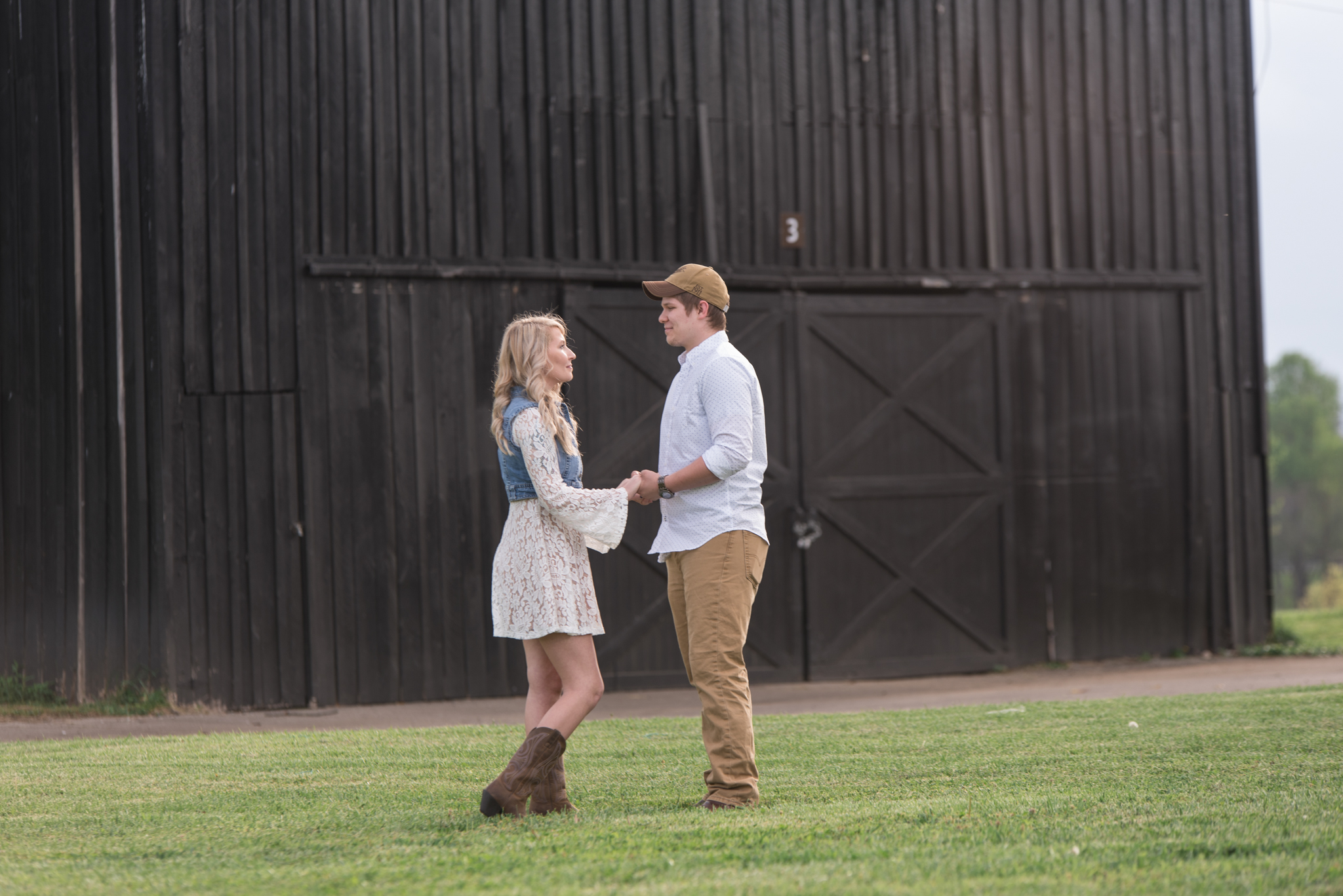 Lexington KY engagement session, couple holding hands in front of barn