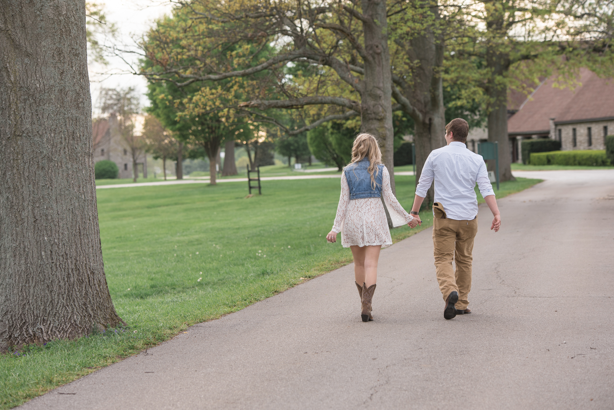 Lexington KY engagement photo of couple walking down road at Keeneland