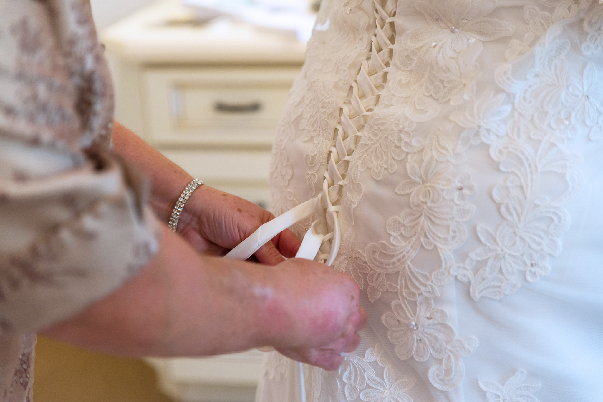 Bride getting her dress laced up