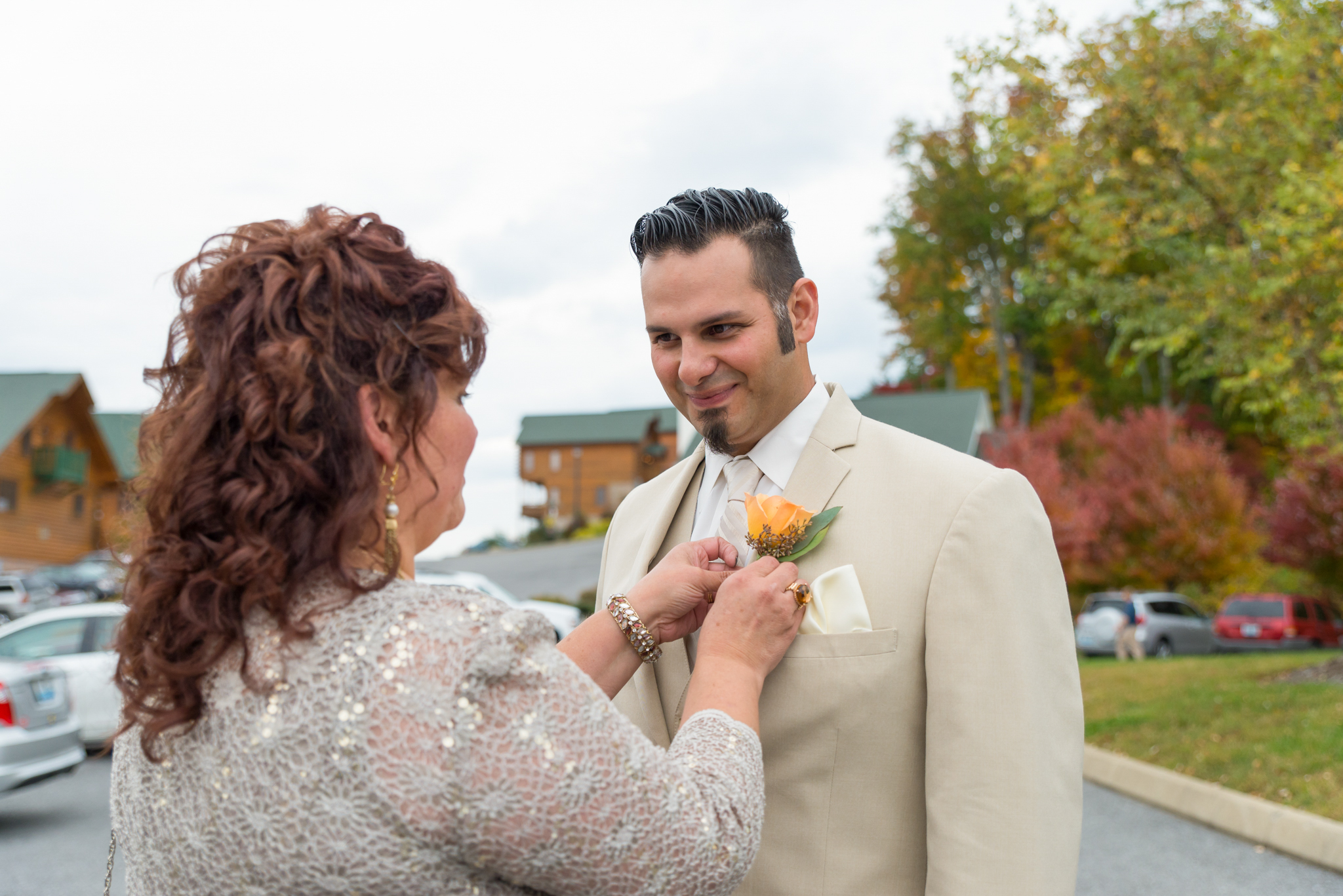 Groom's mother placing his boutonniere