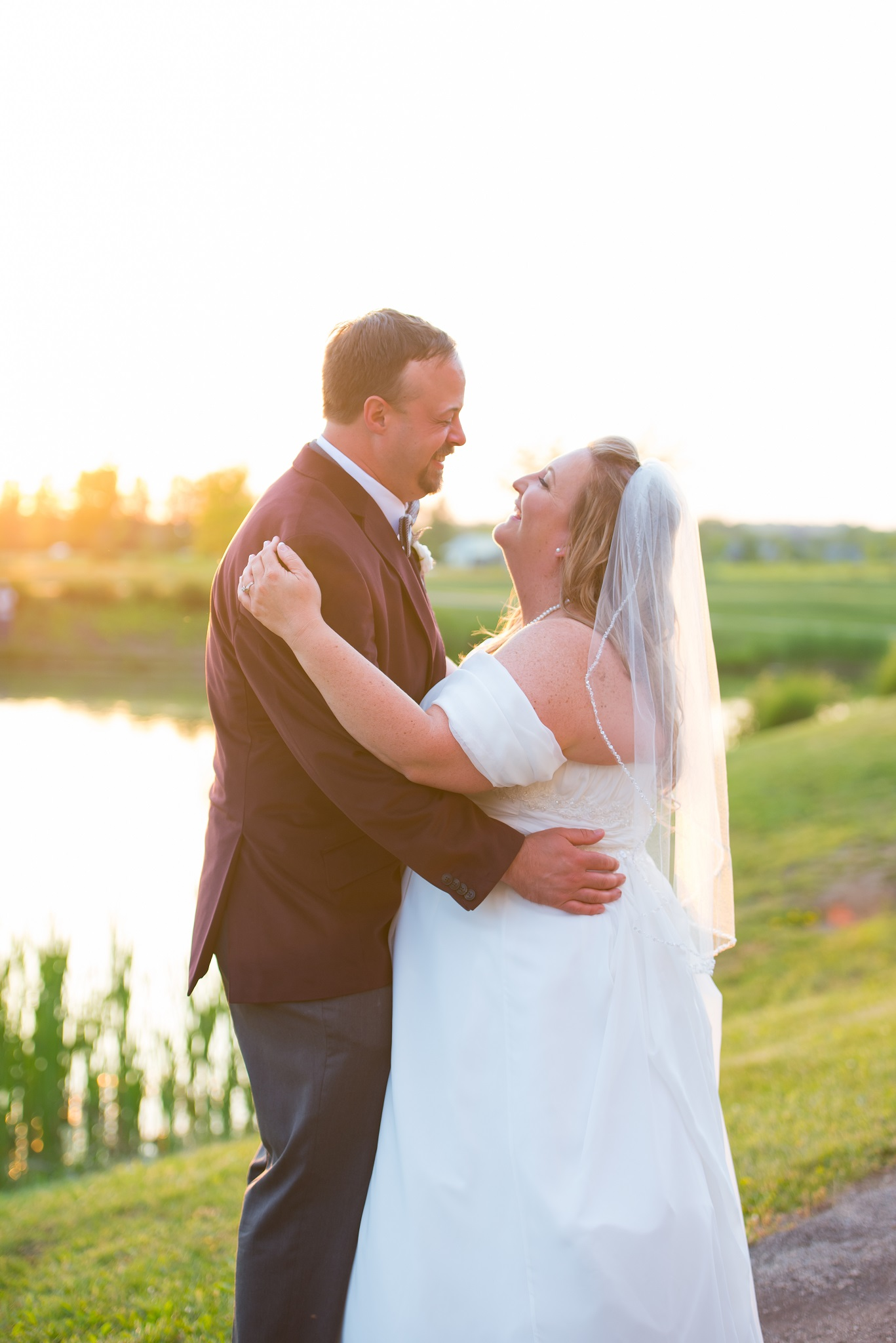 bride and groom in front of pond at Mulhauser Barn in West Chester, OH