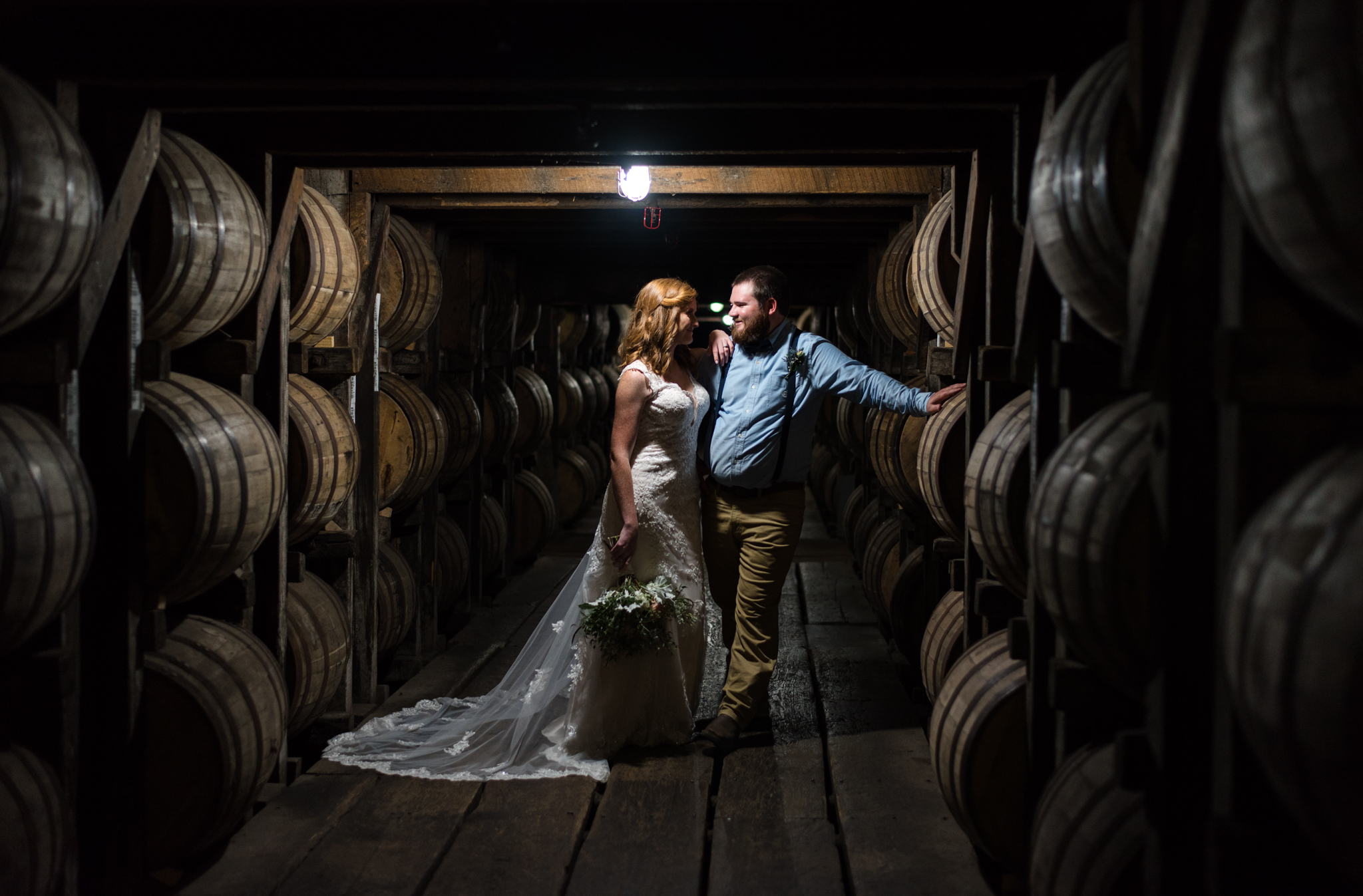 bride and groom in barrel house at buffalo trace distillery